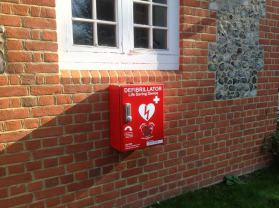 An image of a defibrilator attached to the outside wall.
